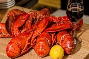 Cooked whole lobsters with a glass of wine